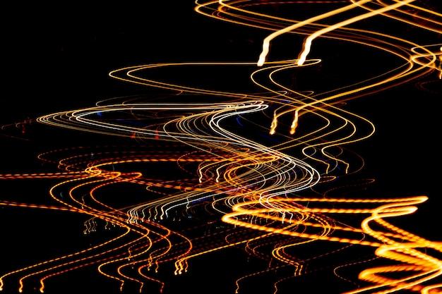 Streszczenie kolorowe linie lampek nocnych na czarnym tle.