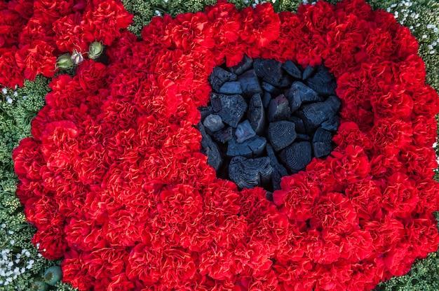 Streszczenie maku z czerwonych goździków i czarnego węgla. kwiaty w tle. ikiebana czerwonych goździków.