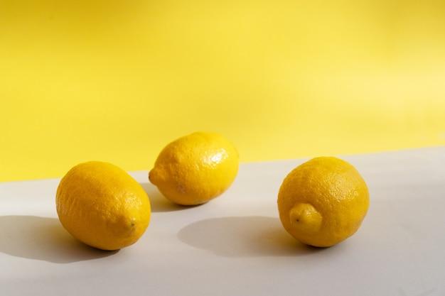 Streszczenie modne tło z papieru czerpanego z trzema owocami cytryny w ostatecznym szarym i rozświetlającym żółtym kolorze