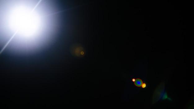 Streszczenie naturalny rozbłysk słoneczny lub daleka gwiazda na czarnym tle - obraz