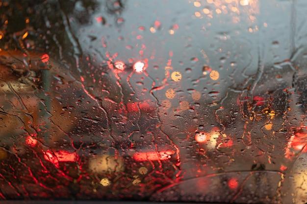 Streszczenie niewyraźne deszcz, gdy samochód jest w środku drogi w nocy światło tylne samochodu