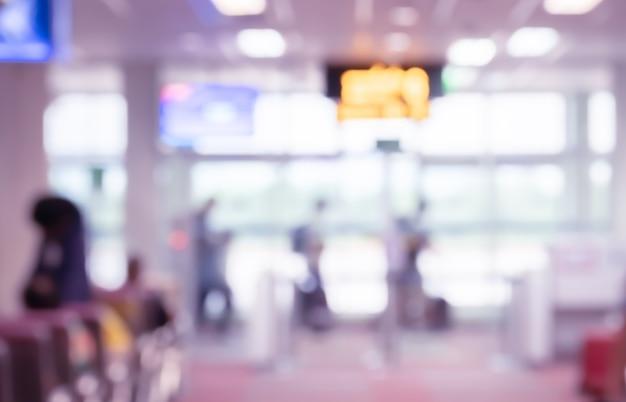 Streszczenie niewyraźne tło pasażerów chodzących na lotnisku w strefie wejścia na pokład