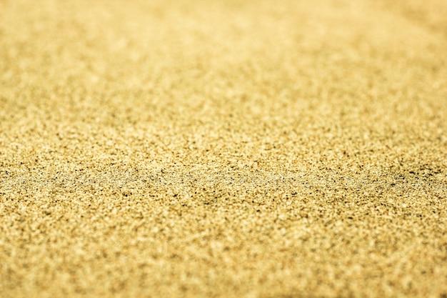 Streszczenie niewyraźne tło słoneczny z ziaren żółtego piasku.