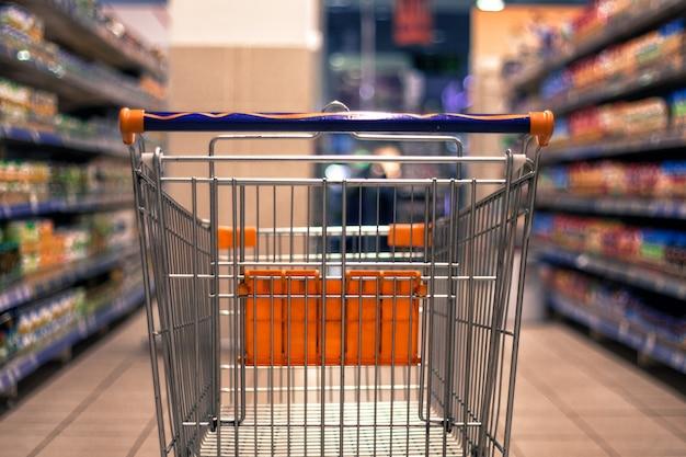 Streszczenie niewyraźne zdjęcie wózka na zakupy lub wózka w domu towarowym z tłem bokeh