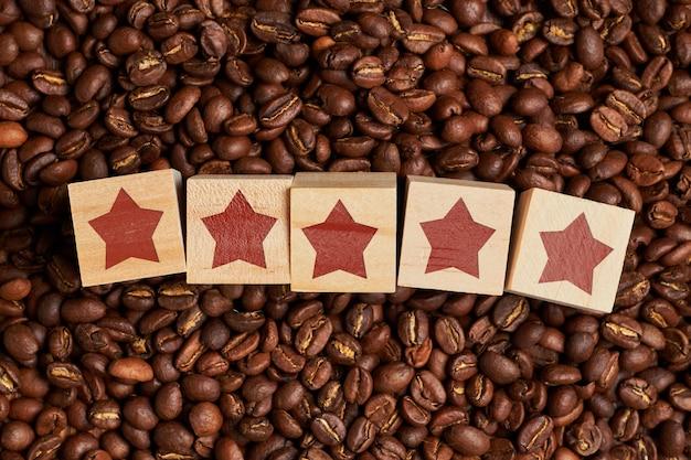 Streszczenie oceny pięciu gwiazdek na drewnianych kostkach na ziarnach kawy. koncepcja najlepszej kawy.