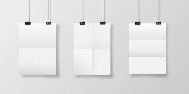 Streszczenie plakatu z wiszące złożone papiery. wisząca makieta plakatu papieru a4. trzy kartki papieru wiszą na tle ściany z nałożonymi cieniami z okna