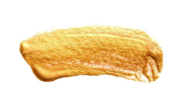 Streszczenie pociągnięcia pędzlem złotą farbą na papierze