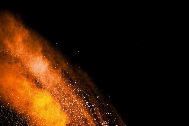 Streszczenie pomarańczowy proszek wybuch na czarnym tle