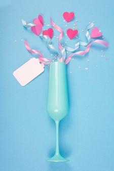 Streszczenie powierzchni z papierowymi sercami, niebieski kieliszek do szampana na walentynki