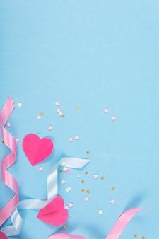 Streszczenie powierzchni z papierowymi sercami, wstążkami na walentynki