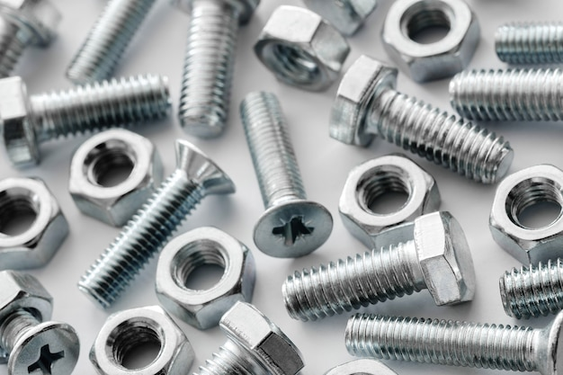 Streszczenie przemysłowe teksturowane metalowe tło z wieloma metalowymi nakrętkami i śrubami