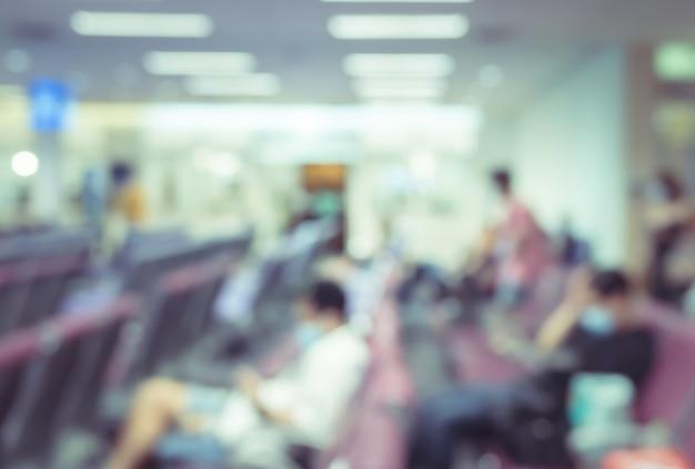 Streszczenie rozmycie i niewyraźne wnętrze terminalu lotniska z podróżnymi na tle. poczekalnia