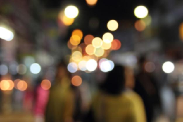 Streszczenie rozmycie nocnego targu, ludzie chodzą na zakupy relaksujący