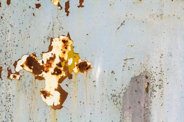 Streszczenie tekstury pionowej nieczysty rdzewiejącej blachy z łuszczącą się farbą i rozległej korozji z smugami rdzy.