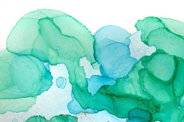 Streszczenie tło akwarela przezroczyste krople. tekstura brokatu zielony, niebieski i złoty.