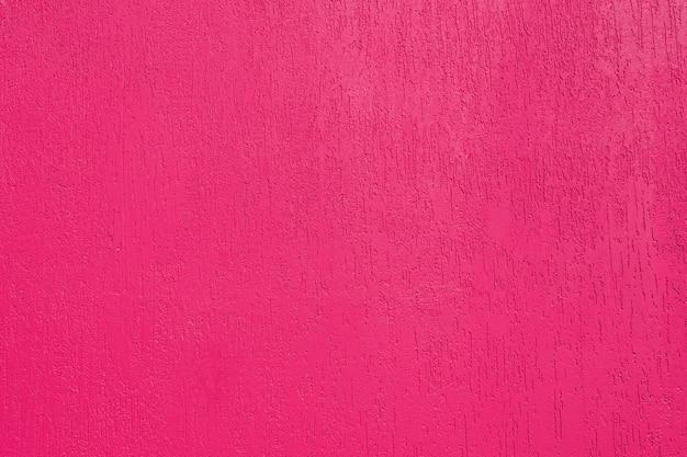 Streszczenie tło i tekstura otynkowane ściany o jasnym różowym kolorze z fakturą kornika. oświetlony jasnym słońcem.