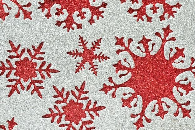 Streszczenie tło i tekstura srebrny błyszczący materiał z wyciętymi płatkami śniegu o różnych kształtach na czerwonym błyszczącym tle.