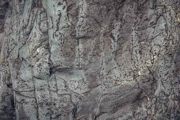 Streszczenie tło kamień. szorstka powierzchnia szarej skały z pęknięciami i naturalnym wzorem, z bliska. tekstura do projektowania.
