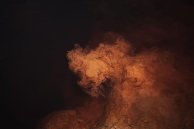 Streszczenie tło, kolor mgławicy czerwony, pomarańczowy i brązowy, kreatywna płynna tekstura, ciemność i światło, czerwona woda rzeczna i pył unoszący się w wodzie