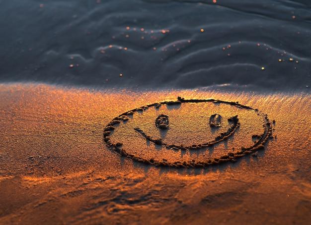 Streszczenie tło lato ze złotym światłem zachodu słońca na piasku plaży i uśmiechniętą twarz emoji