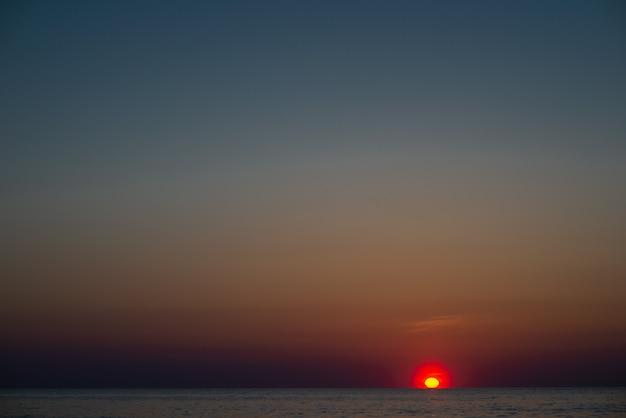 Streszczenie tło lato ze złotym światłem zachodu słońca na piasku plaży i wodzie