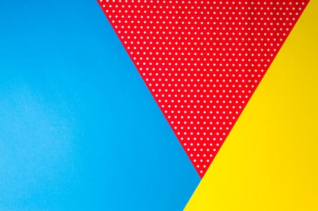 Streszczenie tło niebieskie, żółte i czerwone kropki papieru.