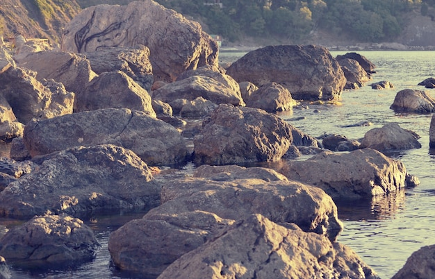 Streszczenie tło ogromnych kamieni na brzegu, filtr