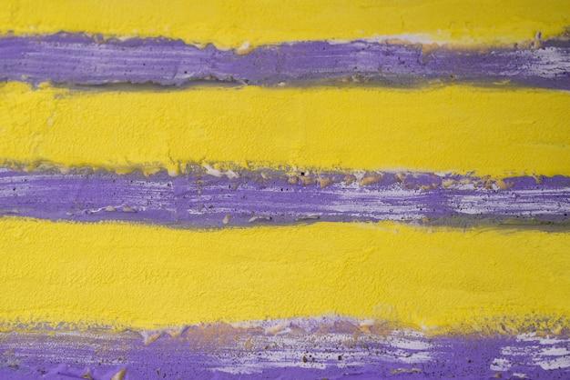 Streszczenie tynk tekstury w jasnych odcieniach żółtego i fioletowego.