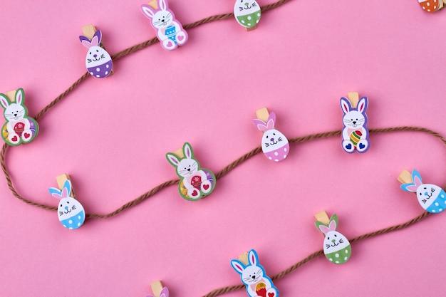 Streszczenie wielkanocna kompozycja. brązowa nić i ozdobne króliki wielkanocne na różowym tle.