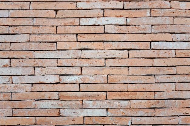 Streszczenie wyblakły teksturowanej czerwonej cegły ściany tło. cegła wnętrza z cegły, stara, czysta betonowa siatka, nierówna, pozioma tapeta architektoniczna.