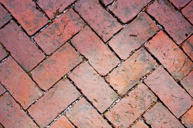 Streszczenie wyblakły teksturowanej czerwonej cegły ściany tło. murowane wnętrze z kamienia, stara, czysta betonowa kratka nierówna