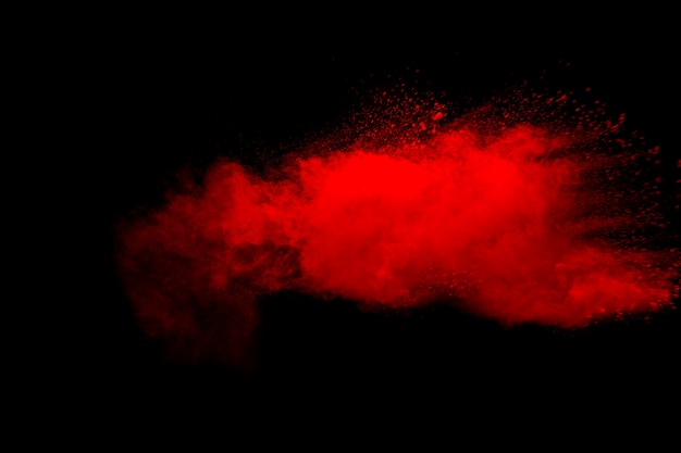 Streszczenie wybuch czerwonego pyłu na czarnym tle. zatrzymaj ruch rozprysku czerwonego proszku.