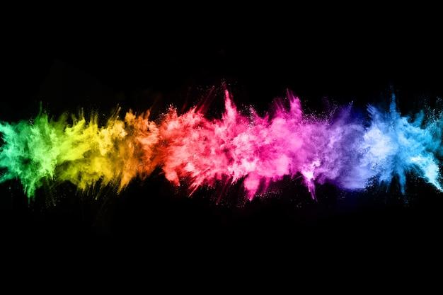 Streszczenie wybuchu pyłu kolorowe na czarnym tle.