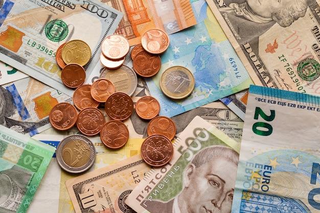 Streszczenie wykonane z różnych metalowych monet, banknotów amerykańskich, ukraińskich i waluty banknotów euro. pieniądze i finanse, udane inwestycje.