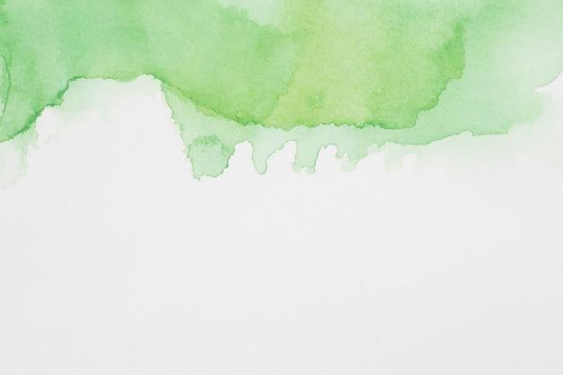 Streszczenie zielone plamy farby na białym papierze