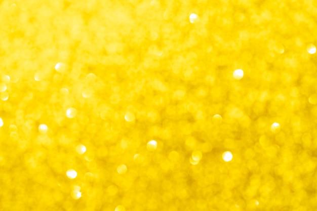 Streszczenie złoty żółty niewyraźne tło bokeh. błyszczące świecące światła. świąteczny i uroczysty tło na wakacje, boże narodzenie i nowy rok, zdjęcie stockowe