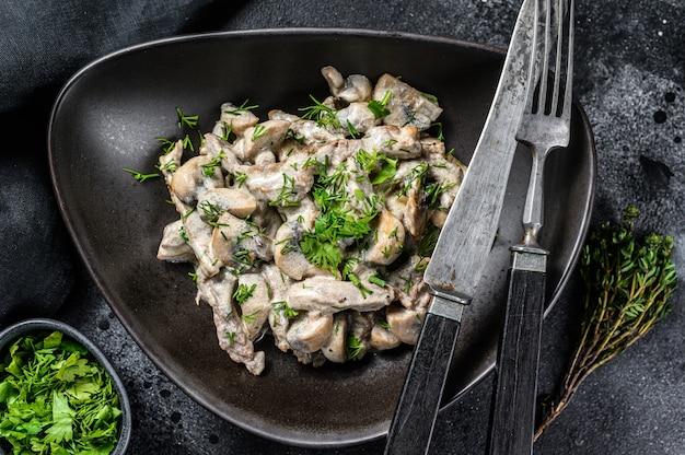 Stroganow wołowy z pieczarkami i świeżą natką pietruszki na talerzu