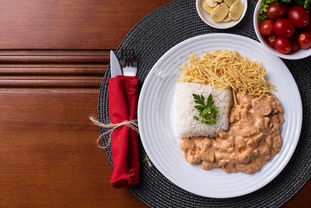 Stroganow z kurczaka w towarzystwie ryżu, sałatki i słomy ziemniaczanej.