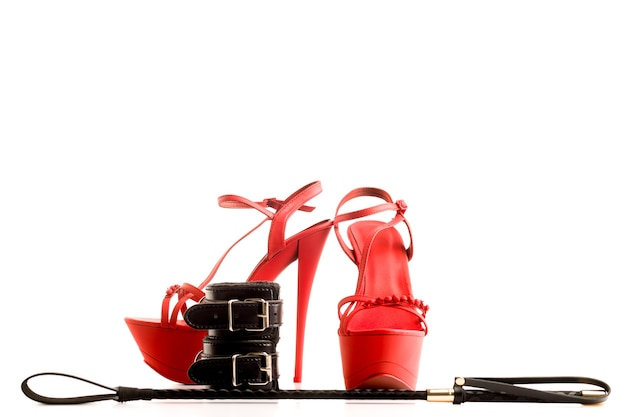 Strój bdsm do gier erotycznych dla dorosłych. czerwone buty na wysokim obcasie striptiz i kajdanki, bat na białym tle na białym tle - obraz