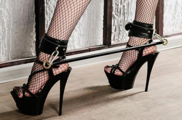 Strój bdsm do gier erotycznych dla dorosłych. nogi kobiet w czarnych pończochach w siateczce na wysokich obcasach spętane kajdankami i bandażem - zdjęcie