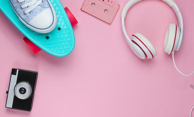 Strój hipster. deskorolka, słuchawki, kaseta audio, trampki, aparat retro na różowym tle. kreatywny minimalizm modowy. minimalna letnia zabawa. pop art. 80s. skopiuj miejsce.