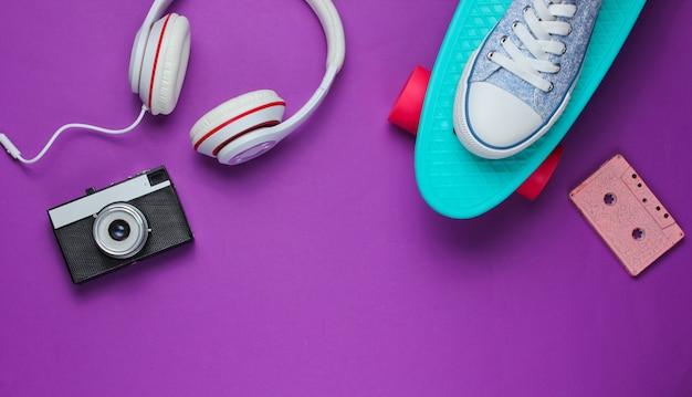 Strój hipster. deskorolka, słuchawki, kaseta audio, trampki, retro aparat na fioletowym tle. kreatywny minimalizm modowy. minimalna letnia zabawa. pop art.