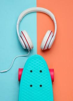 Strój hipster. deskorolka ze słuchawkami na kolorowym pastelowym tle. kreatywny minimalizm modowy. modny stary modny styl. minimalna letnia zabawa. koncepcja muzyki