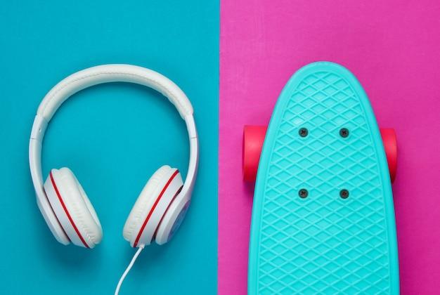 Strój hipster. deskorolka ze słuchawkami na kolorowym tle. kreatywny minimalizm modowy. modny stary modny styl. minimalna letnia zabawa. koncepcja muzyki. widok z góry