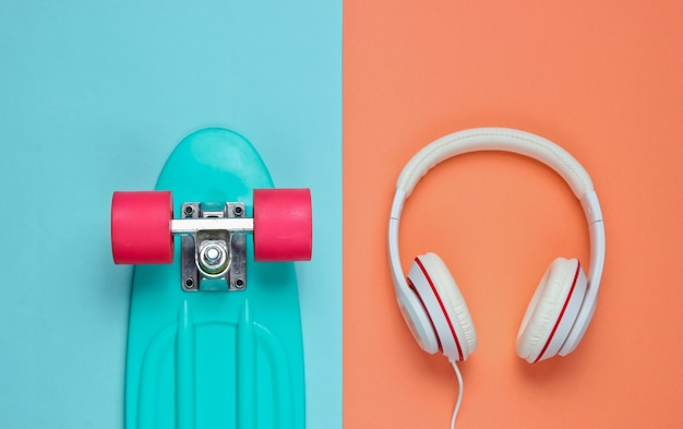 Strój hipster. deskorolka ze słuchawkami na kolorowym tle. kreatywny minimalizm modowy. modny stary modny styl. minimalna letnia zabawa. koncepcja muzyki.