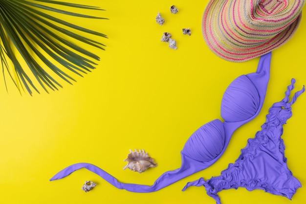 Strój kąpielowy bikini z palmami tropikalnymi na żółtym tle. widok z góry kobiety stroje kąpielowe i akcesoria plażowe z miejsca kopiowania
