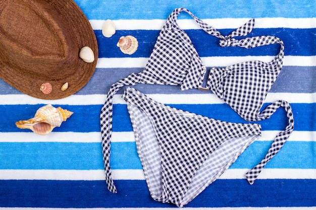 Strój kąpielowy z akcesoriami plażowymi na niebieskim tle