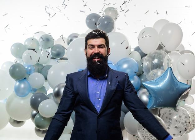 Strona człowieka z balonów. spadające konfetti. urodziny mężczyzna w garniturze z balonami z helem. uroczystość, święta, koncepcja strony. uśmiechnięty mężczyzna rzuca konfetti. szczęśliwy biznesmen z latającym konfetti.