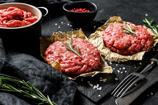 Strona główna ręcznie robione burgery z surowego mięsa mielonego wołowego. ekologiczne mięso hodowlane. czarne tło. widok z góry