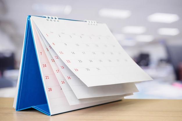 Strona kalendarza przewracana na stole w biurze